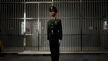 A Chinese paramilitary police man stands guard outside a prison entrance (Getty Images)