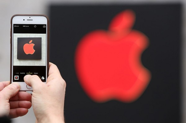 A visitor photographs a red Apple logo with an iPhone at the Apple Store on Dec. 1, 2014 in Berlin, Germany.