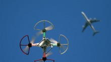 A drone is flown for recreational purposes as an airplane passes nearby in the sky above Old Bethpage, New York on September 5, 2015.