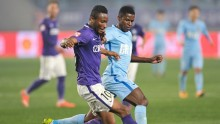Tianjin Teda midfielder John Obi Mikel (L) competes for the ball against Jiangsu Suning's Ramires