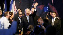 Israeli Prime Minister Benjamin Netanyahu (C) waves to supporters at party headquarters in Tel Aviv March 18, 2015.