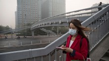 A Chinese woman wears a mask as she crosses a foot-bridge