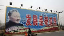 A woman rides a tricycle past a giant poster of late Chinese leader Deng Xiaoping in Beijing.