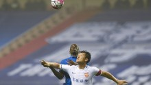 Yanbian Funde defender Cui Min (in white) competes for the ball against Shanghai Shenhua's Demba Ba