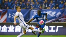 Yanbian Funde defender Nikola Petkovic (L) competes for the ball against Shanghai Shenhua's Demba Ba