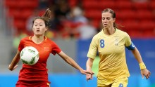 China defender Wu Haiyan competes for the ball against Sweden's Schelin Lotta