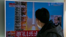 People watch a television screen showing a breaking news on North Korea's long-range rocket launch