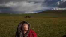 A Tibetan Buddhist monk sits on the grasslands outside a monastery next to a government resettlement community for former nomads at Tibetan Plateau in Yushu County, Qinghai, China