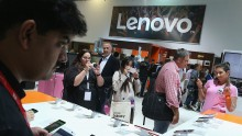 Visitors look at smartphones at the Lenovo stand at the 2015 IFA consumer electronics and appliances trade fair on September 4, 2015 in Berlin, Germany.