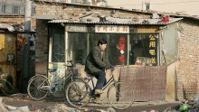 A cyclist rides past a public telephone booth in a poor slum area on January 2, 2005 in Beijing, China.