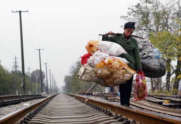 A Chinese migrant worker carrying rubbish walks on a railway December 6, 2004 in Wuhan, Hubei Province of China.