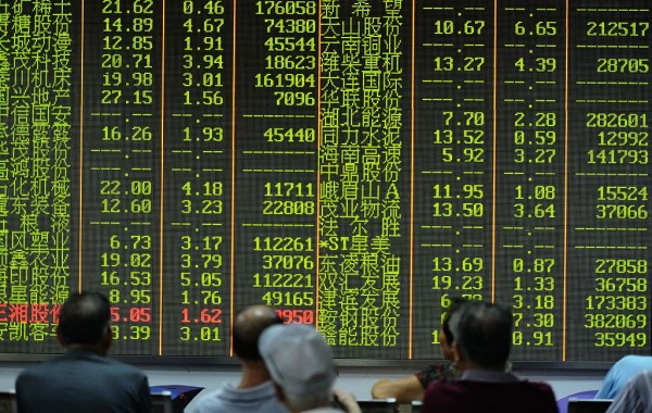 An investor observes the stock market at an exchange hall on August 21, 2015 in Hangzhou, Zhejiang Province of China.
