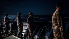 Security ship crews of Ministry of Maritime Affairs and Fisheries, stand on the main deck during a patrol in the South China Sea on August 17, 2016 in Natuna, Ranai, Indonesia.
